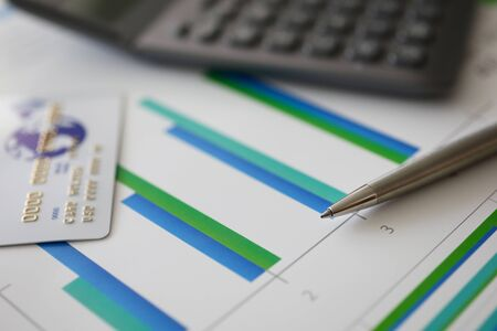 Pen, calculator and plastic debit card on graph Banco de Imagens