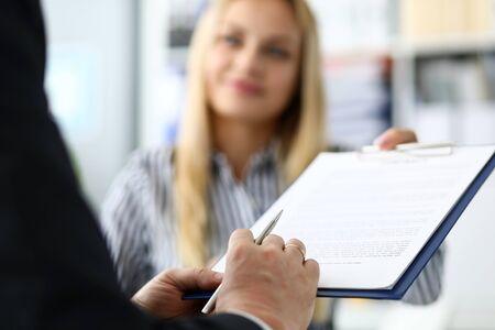 Agente inmobiliario femenino sonriente que ofrece el documento de visitante masculino para firmar