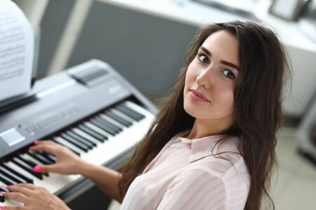 Attractive lady playing piano 스톡 콘텐츠 - 129416119