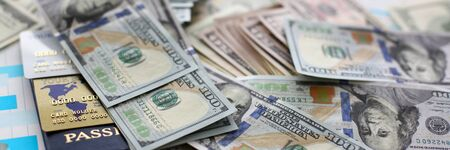 Huge pile of US money passport and bank cards lying on financial statistics graphics Standard-Bild