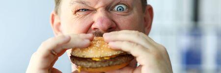 Funny bearded man with idiot facial expression eating big burger Фото со стока