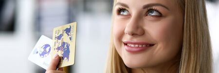 Beautiful blonde adult caucasian woman in office hold two credit cards