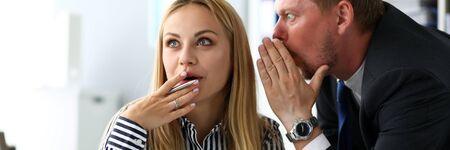 Männlicher Angestellter teilt geheimes Wissen mit Kollegin