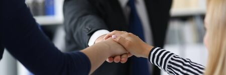 Focus on male and female hands showing friendly collective gesture. Friendly team of joyful businesspeople sitting in big modern office. Teamwork concept. Blurred background Stock Photo