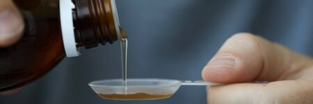 Close-up of male hands holding holding bottle of cough expectorant syrup and pouring it with measuring spoon. Ill man taking medicine. Healthcare and treatment concept. Blurred background