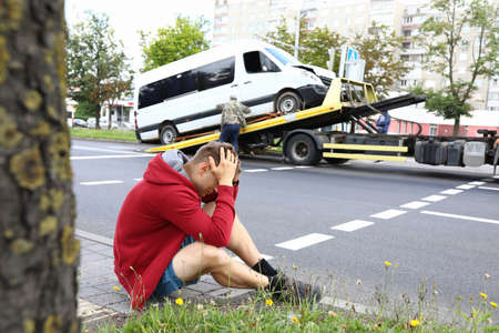 Man sits on side of road holding his head with his hands next to wrecked car after car accident