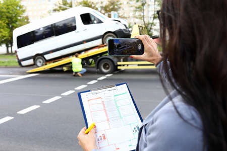 Insurance agent records accident on his phone and evaluates car.