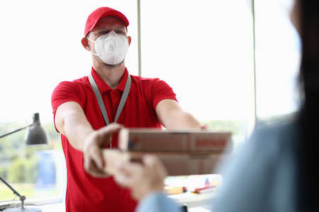 Courier wearing protective mask delivers pizza closeup Stock fotó