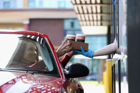 Woman in convertible car picks up tea and coffee in Mcdrive Reklamní fotografie