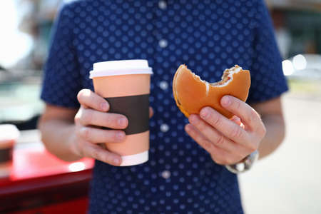 Man holds glass with hot coffee and hamburger in his hand