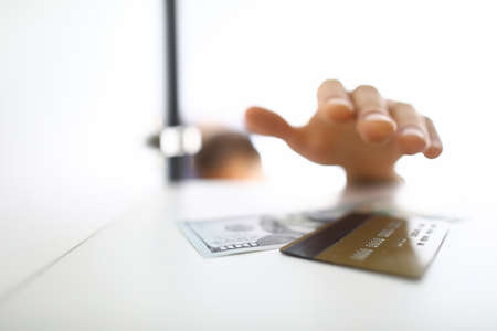 Mans hand reaches for paper bill and card