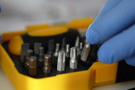 Gloved hand holds set of screwdriver bit sprocket Zdjęcie Seryjne