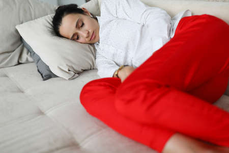 Woman in business clothes is sleeping on couch. 스톡 콘텐츠