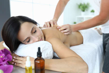 Woman in spa is being massaged by masseur.