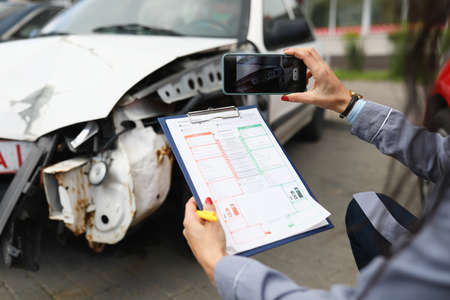 Insurance agent takes pictures of crashed car on his smartphone and fills out the insurance Archivio Fotografico