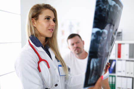 Woman doctor examines an x-ray with patient. Standard-Bild