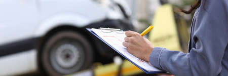 Insurance agent fills out paperwork after accident.