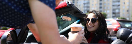 Woman sits in car man meets her closeup