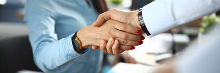 Businesswoman and businessman shaking hands in office. Business agreement and arrangement concept