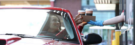 Woman in car picks up her coffee concept