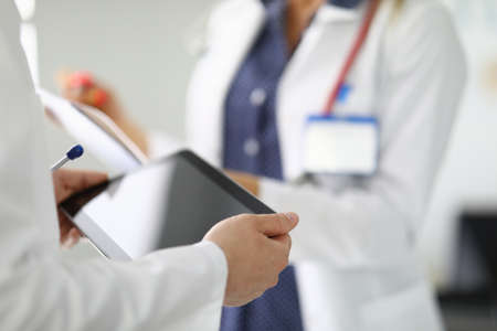 Two people in white coat one holding tablet second clipboard. Banco de Imagens