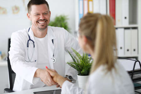 Doctors colleagues smile and shake hands in office.