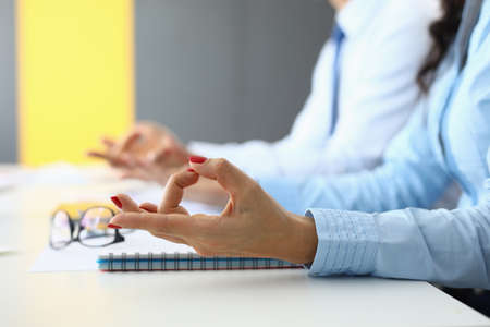 Female and male hands are connected in yoga fingers for meditation at table in office. Foto de archivo