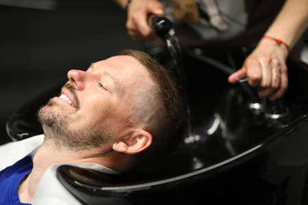 Master washes mans head in sink in hairdresser.