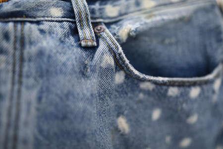 Jeans pocket made of blue frayed fabric closeup.