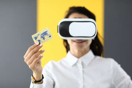 Woman is wearing virtual reality glasses in her hands she is holding bank credit card