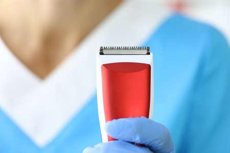 Man in blue uniform holds shaving machine closeup Banque d'images