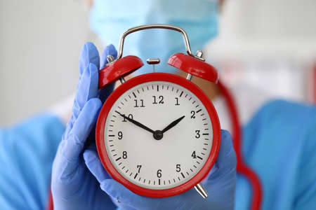 Doctor in gloves holds red alarm clock closeup.