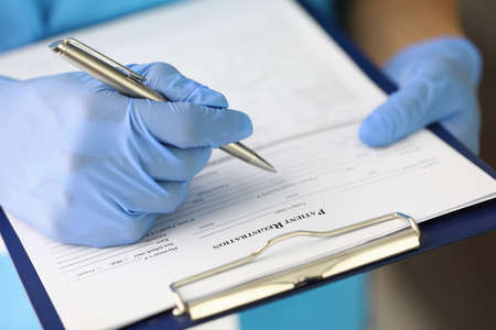 Gloved hand holds clipboard and pen and fills out patient registration form