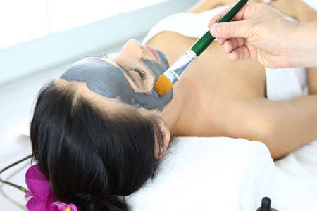 Woman lies on her face applying regenerating face mask with brush.