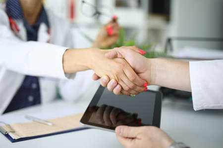 Handshake of two doctors one is holding tablet.