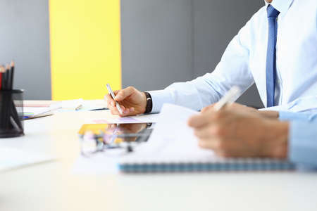 Businessmen hold pens and documents at their desk. 版權商用圖片