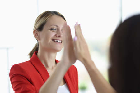 Businesswoman smiles and gives five to her colleague. Stock fotó