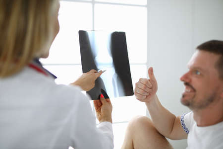 Doctor woman holds an x-ray of leg beside the patient he smiles and shows thumbs up