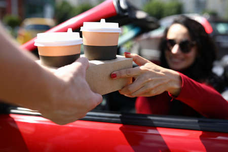 Woman in a car in sunglasses is handed drinks in glasses.