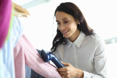 Woman ironing shirt with steamer on hanger