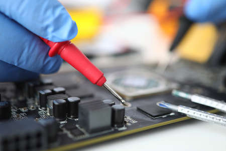 Gloved master holds probe over microcircuit closeup Stock Photo