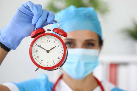 Doctor in medical protective mask holds red alarm clock in his hands
