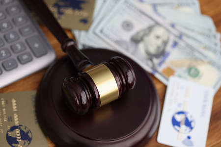 Wooden gavel for judge lies on table next to one hundred dollar bills and bank credit cards. Stock fotó