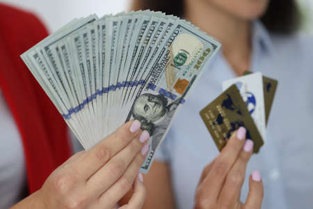 Female hands hold fan of one hundred American dollar bills and credit bank cards.