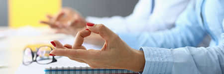 Female and male hands are connected in yoga fingers for meditation at table in office.