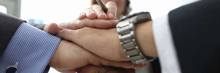 Businesswoman and two businessmen folded their hands together in office closeup