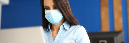 Businesswoman in medical protective mask sits at her desk and works on laptop.
