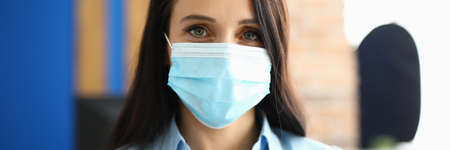 Portrait of businesswoman in protective medical mask in office