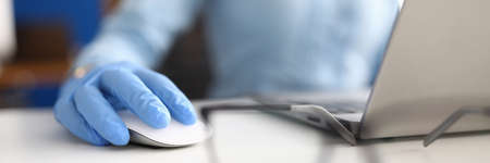 Hand in blue medical glove lies on computer mouse next to glasses and laptop