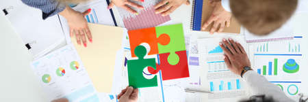 Businesspeople at table with business indicators and colored puzzle Foto de archivo